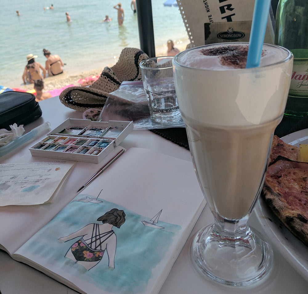 painting at a beachside cafe in Croatia with travel watercolors