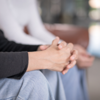 Claspened hands in the foreground with a second pair of clasped hands in a blurred background.