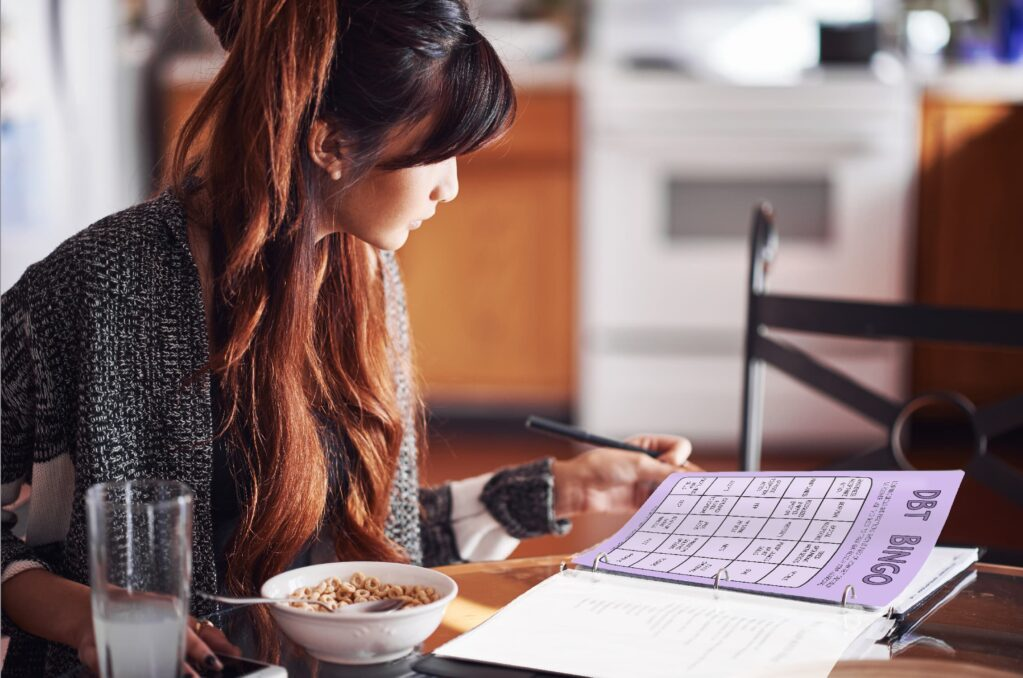 A young woman reading a colorful printed DBT worksheet.