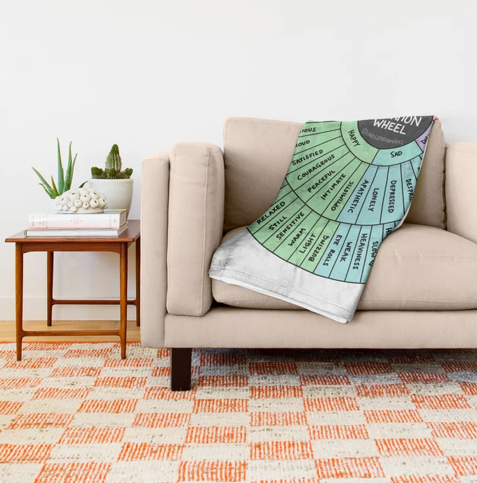 A blanket tossed over a sofa printed with the emotion sensation wheel.